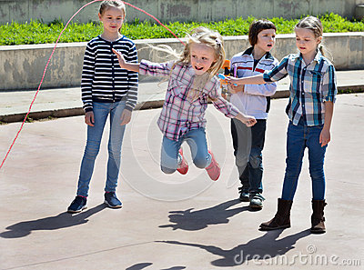 Children playing skipping rope jumping game Stock Photo