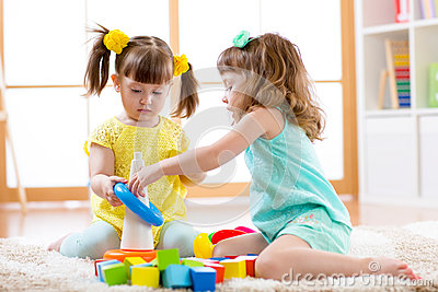 Children playing together. Toddler kid and baby play with blocks. Educational toys for preschool and kindergarten child Stock Photo