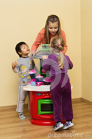 Children playing with toy cooker