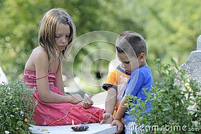 children praying in cemetery