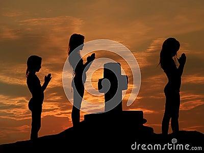 Children praying at sunset