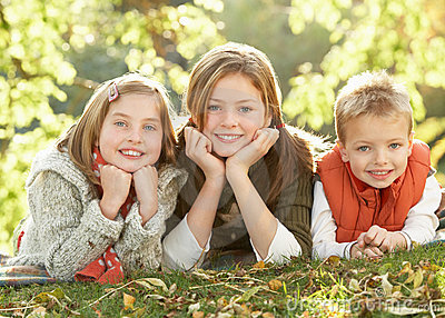 Children Relaxing Outdoors In Autumn Landscape