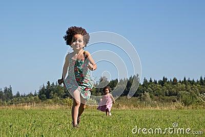 Children running across grass field