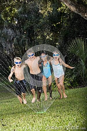 Children running through lawn sprinkler together