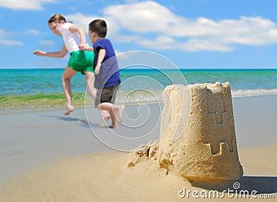 Children running from sand castle
