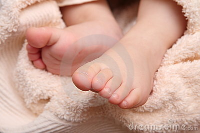 Children s feet in the hands of the mother