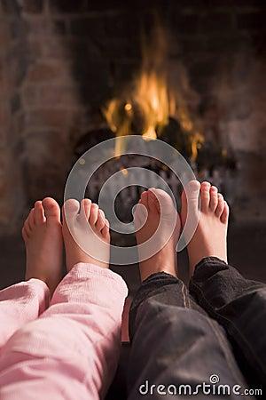 Children s feet warming at a fireplace