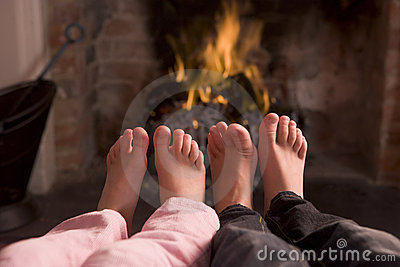 Children s feet warming at a fireplace