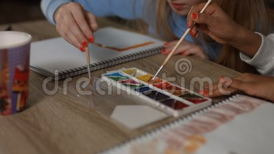 Children`s hands with paintbrushes painting stock footage
