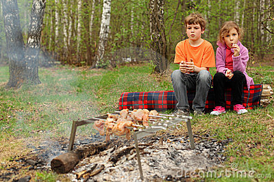 Children sit near campfire with grill and barbecue