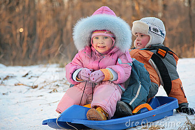 Children  sits on plastic sled