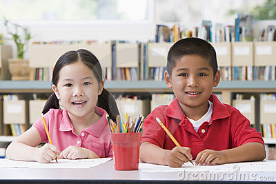 Children sitting at desk and writing in classroom