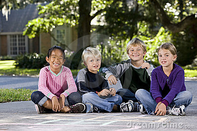 Children sitting in a row outdoors