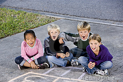 Children sitting together laughing on driveway
