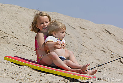 Children sledding down sand dune