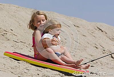 Children sledding down sand dune