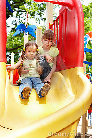 Children on slide outdoor in park.