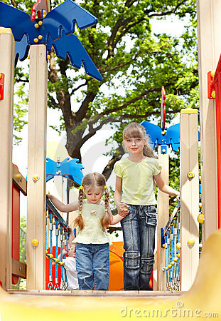 Children on slide outdoor in park.