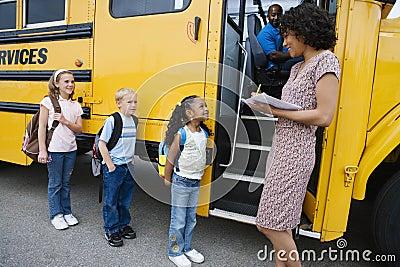 Children Standing In A Line By School Bus