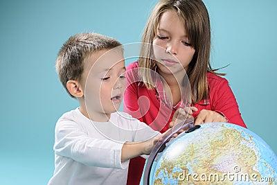 Children studying destinations on globe
