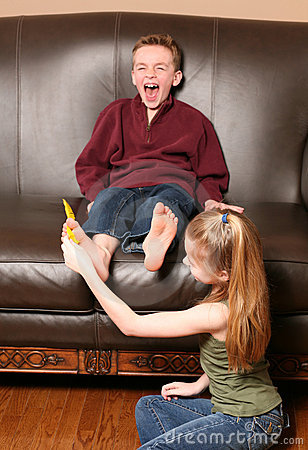 Children tickling feet with feather
