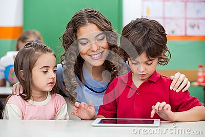 Children Using Digital Tablet With Teacher