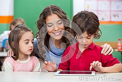 Children Using Digital Tablet With Teacher