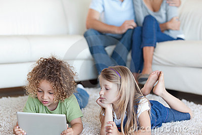 Children using a tablet computer while their parents are watchin