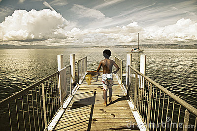 Children walking along a small jetty in Lake Leman Editorial Stock Photo