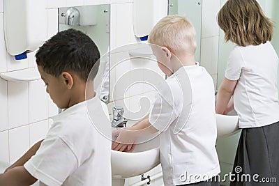 Children washing their hands in a school bathroom