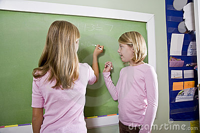 Children writing on blackboard in classroom
