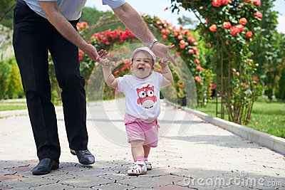 Childs first steps in the fathers strong hands