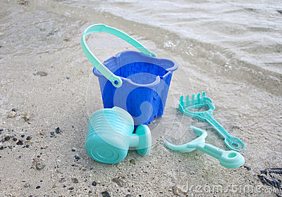 A childs green beach bucket and spades