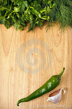 Chili, parsley and garlic on the wooden background