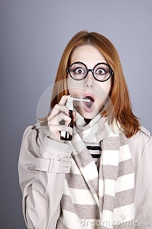Chill red-haired girl in glasses with spray.