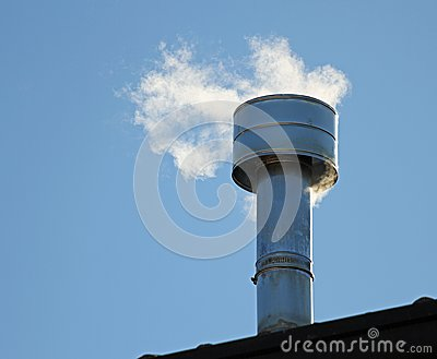 Chimney on the roof with smoke coming out from the boiler