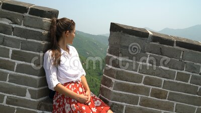 China travel at Great Wall - Woman sitting on the famous tourist attraction. China travel at Great Wall. Tourist woman in Asia relaxing sitting on famous Chinese stock video footage