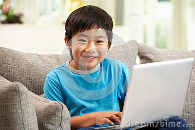 Chinese Boy Using Laptop Sitting On Sofa At Home