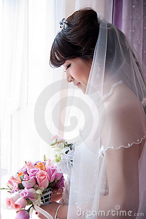 A chinese Bride looking at bouquet