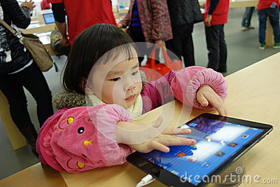 Chinese child playing ipad in the apple store Editorial Stock Photo