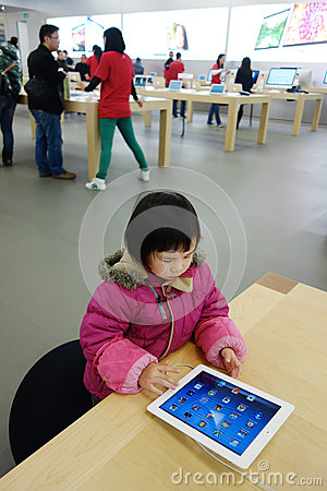 Chinese child playing ipad in the apple store Editorial Photo