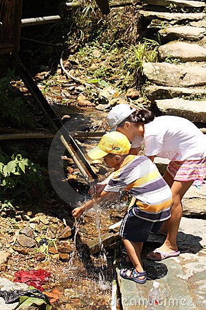Chinese children wash hands in bamboo water drain Editorial Stock Photo