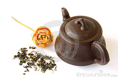 Chinese clay teapot with tea leaves and rose