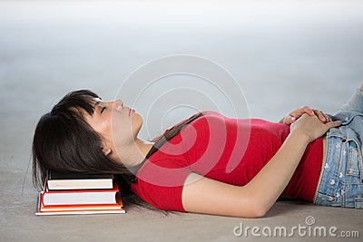 Chinese College Student Sleeping on pile of books