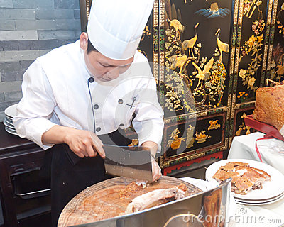 Chinese cooks in cutting roast pork