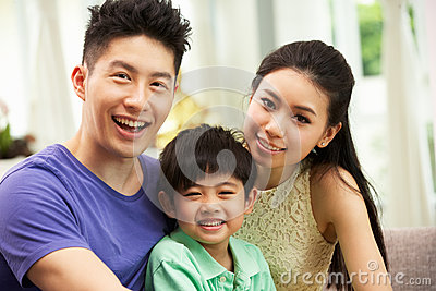 Chinese Family Sitting And Relaxing At Home