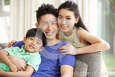 Chinese Family Sitting And Relaxing On Sofa