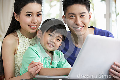 Chinese Family Sitting Using Laptop At Home