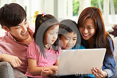 Chinese Family Using Laptop Whilst Relaxing