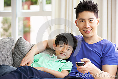 Chinese Family Watching TV On Sofa Together